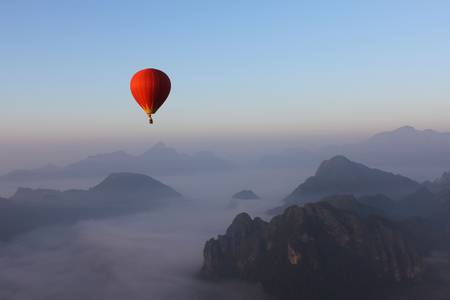 58086710-red-luchtballon-zweven-over-misty-mountain-in-vang-vieng-laos
